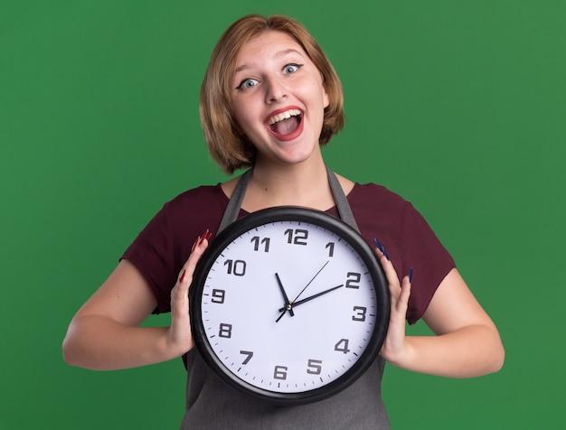 Jovem cabeleireira linda com avental segurando um relógio de parede olhando para a frente, feliz e alegre, sorrindo em pé sobre a parede verde