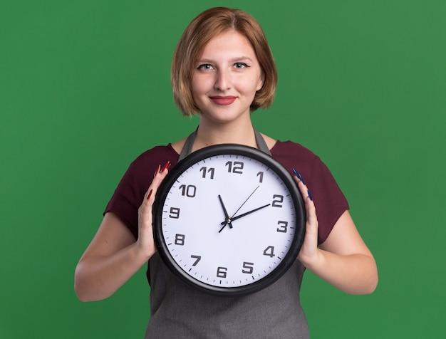 Jovem cabeleireira linda com avental segurando um relógio de parede olhando para frente com um sorriso confiante no rosto em pé sobre a parede verde
