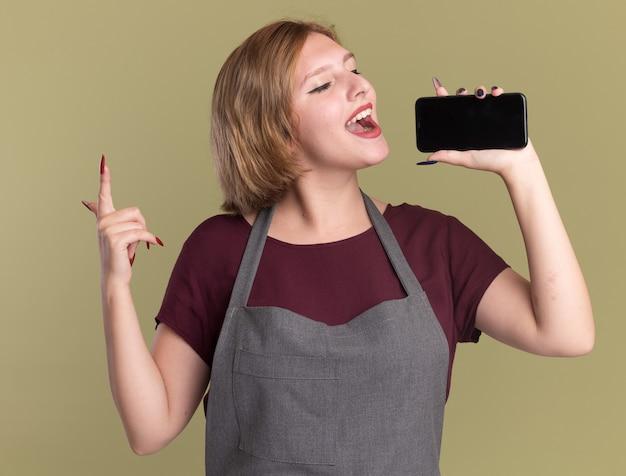 Jovem cabeleireira linda com avental usando o smartphone como microfone cantando feliz e positiva em pé sobre a parede verde