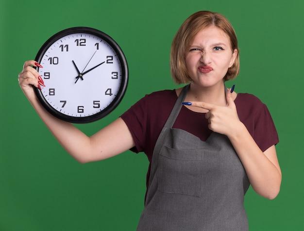 Jovem cabeleireira linda de avental segurando um relógio de parede apontando com o dedo indicador para ela, olhando para a frente, confusa e descontente em pé sobre a parede verde