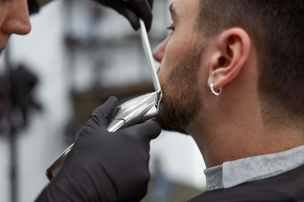 Jovem cabeleireira penteando a barba de uma cliente
