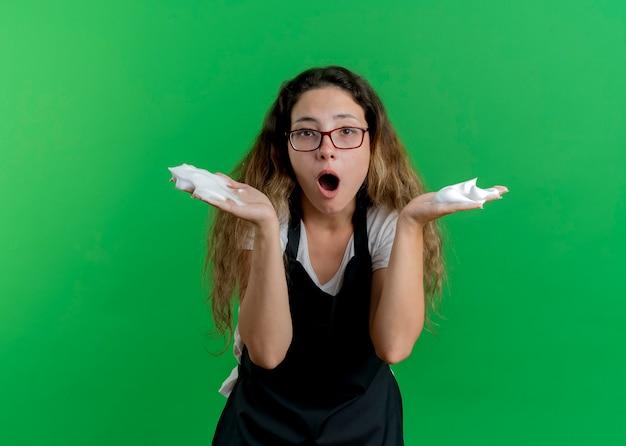 Jovem cabeleireira profissional com avental e espuma de barbear nas mãos, olhando para a frente, surpresa em pé sobre a parede verde
