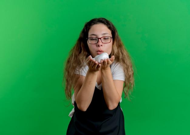Jovem cabeleireira profissional com avental e espuma de barbear nas mãos soprando em pé sobre a parede verde