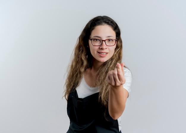 Jovem cabeleireira profissional com avental olhando para a frente, fazendo gesto de dinheiro, esfregando os dedos e sorrindo em pé sobre uma parede branca