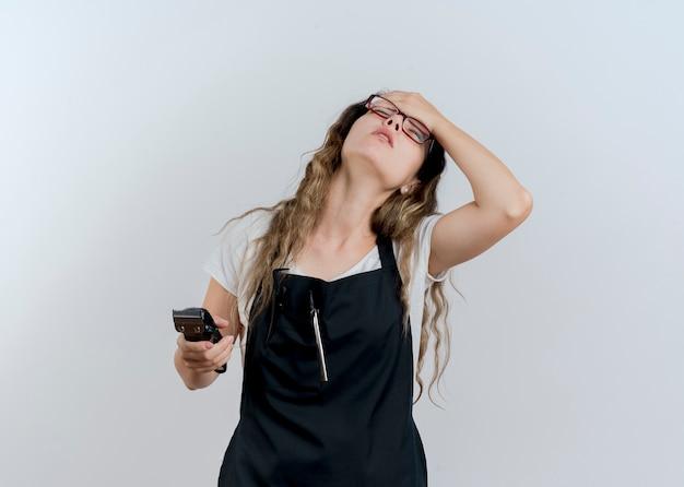 Jovem cabeleireira profissional com avental segurando o aparador e segurando a mão na testa, cansada e entediada em pé sobre uma parede branca
