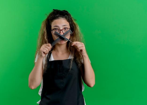 Jovem cabeleireira profissional com avental segurando pentes de cabelo para a câmera, confusa com uma expressão triste