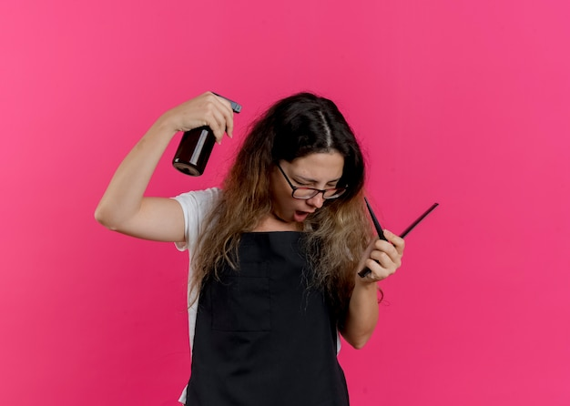 Jovem cabeleireira profissional com avental segurando pentes e borrifando água em spray
