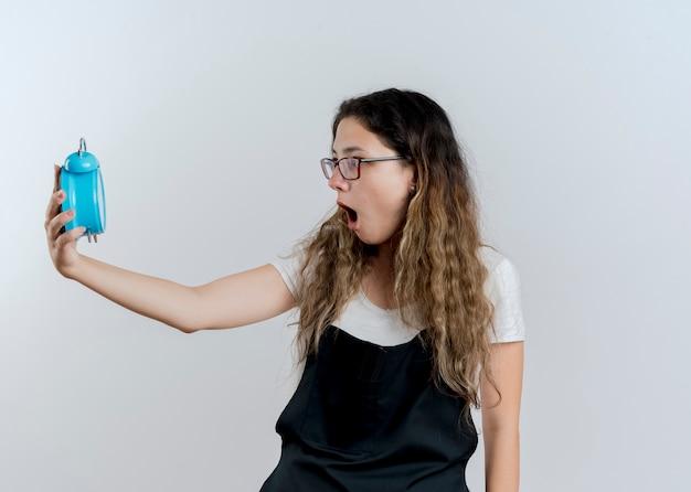 Jovem cabeleireira profissional com avental segurando um despertador e olhando em pânico em pé sobre uma parede branca