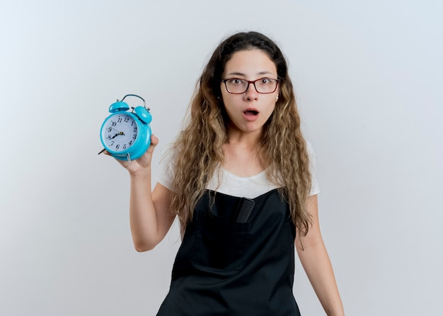 Jovem cabeleireira profissional com avental segurando um despertador, olhando para a frente, chocada em pé sobre uma parede branca
