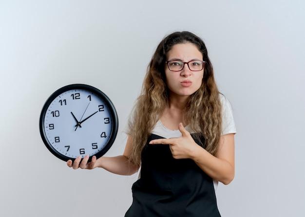 Jovem cabeleireira profissional com avental segurando um relógio de parede apontando com o dedo indicador e ficando descontente em pé sobre uma parede branca
