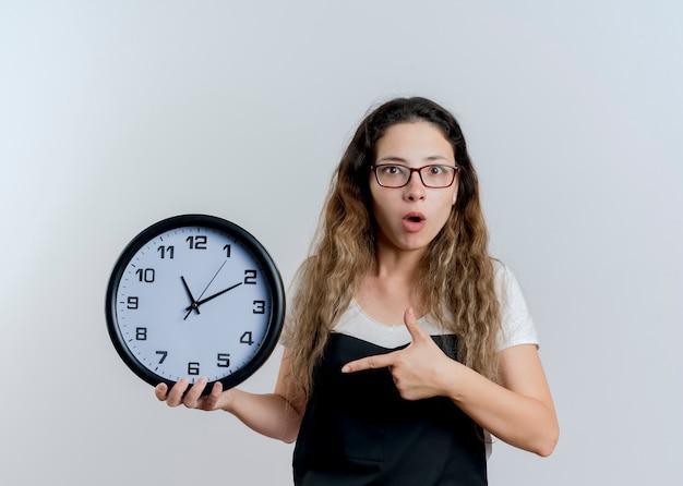 Jovem cabeleireira profissional com avental segurando um relógio de parede com o dedo indicador sendo surpreendida em pé sobre uma parede branca