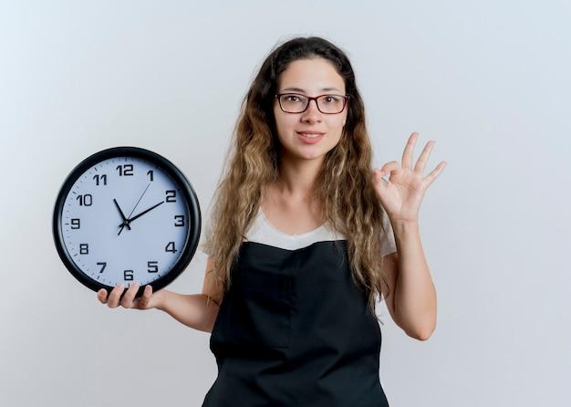 Jovem cabeleireira profissional com avental segurando um relógio de parede, olhando para a frente, mostrando uma placa de ok em pé sobre uma parede branca