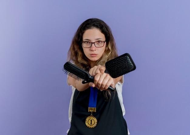 Jovem cabeleireira profissional de avental com medalha de ouro em volta do pescoço segurando escovas de cabelo olhando para a frente com o rosto sério cruzando as mãos em pé sobre a parede azul