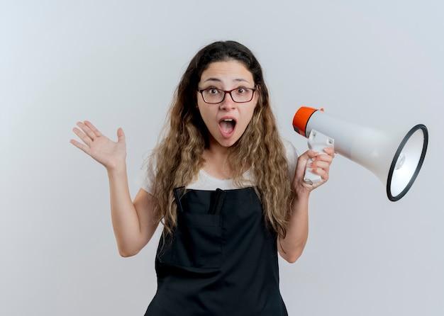 Jovem cabeleireira profissional de avental segurando um megafone, olhando para a frente, gritando e sendo confusa em pé sobre uma parede branca