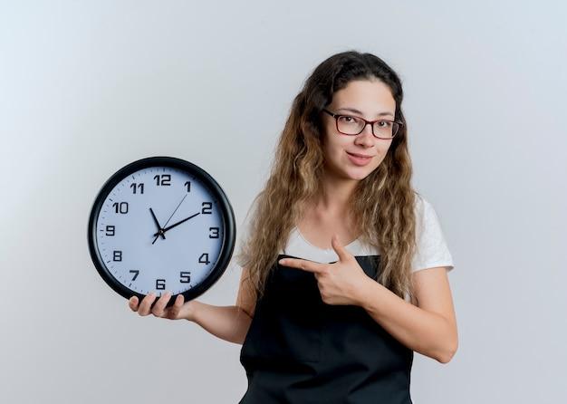Jovem cabeleireira profissional de avental segurando um relógio de parede apontando com o dedo indicador para ele e sorrindo em pé sobre uma parede branca