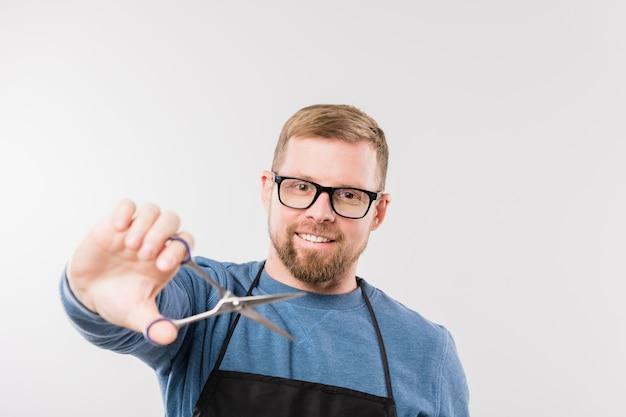 Jovem cabeleireiro barbudo de avental e pulôver azul segurando uma tesoura enquanto vai cortar o cabelo da cliente