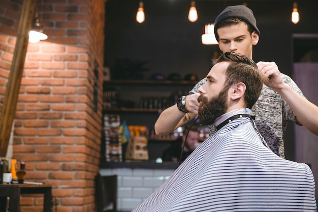 Jovem cabeleireiro bonito fazendo corte de cabelo de homem para um atraente homem barbudo no salão de beleza