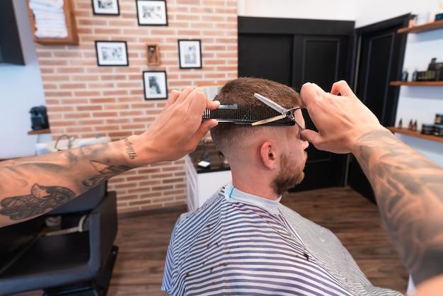 Jovem cabeleireiro com tatuagens cortando o cabelo de um cliente do sexo masculino sob as luzes
