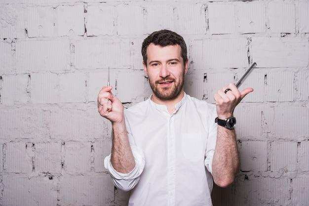 Jovem cabeleireiro, vestindo camisa branca, posando com tesoura e pente, no fundo da parede de tijolo cinza