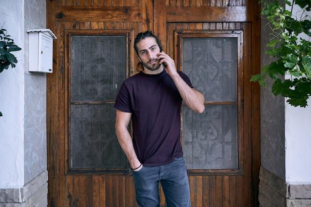 Jovem cabeludo recebendo uma ligação em frente a uma porta de madeira marrom na rua