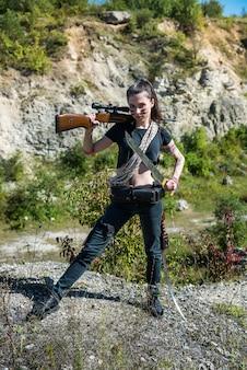 Jovem caçadora feminina em cima com um rifle, no verão na natureza. atirador