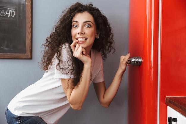 Jovem cacheada de 20 anos abrindo a geladeira silenciosamente enquanto cozinha o jantar no interior da cozinha em casa