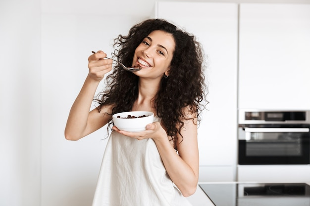Jovem cacheada de 20 anos, vestindo roupas de seda, tomando café da manhã doce na cozinha e comendo granola de chocolate com leite