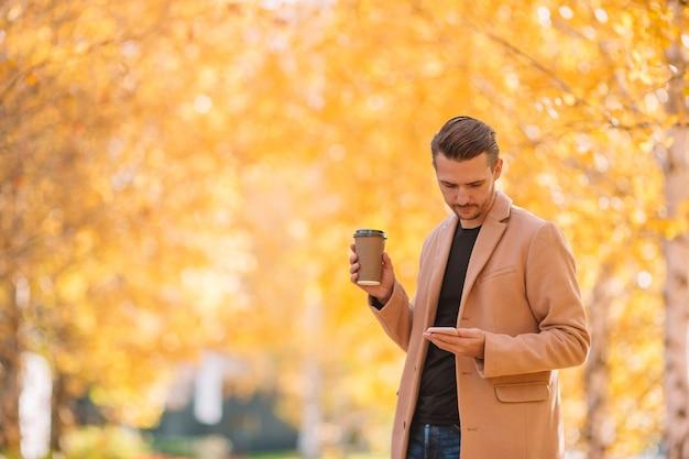 Jovem, café bebendo, com, telefone, em, outono, parque, ao ar livre