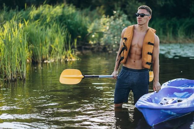 Jovem, caiaque no rio