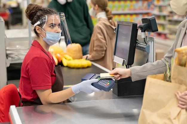 Jovem caixa com uniforme e máscara protetora, luvas e tela olhando para um dos consumidores pagando por produtos com cartão de crédito