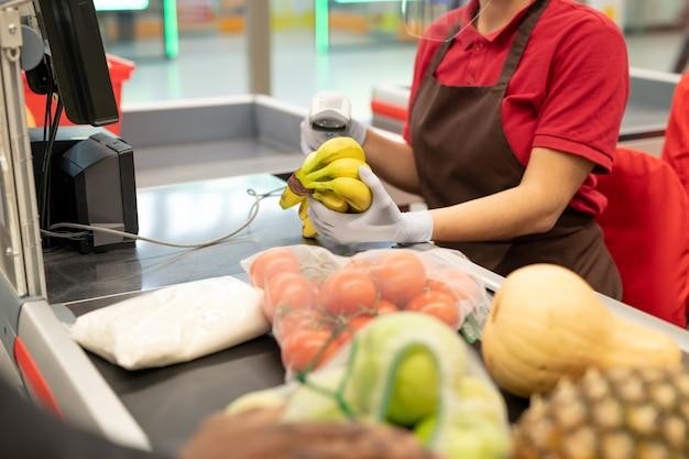 Jovem caixa de uniforme e luvas segurando um cacho de bananas no balcão e digitalizando-o enquanto atende uma das consumidoras