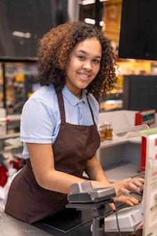 Jovem caixa feliz com cabelo escuro ondulado olhando para você enquanto está no local de trabalho e pressionando o botão da caixa de dinheiro