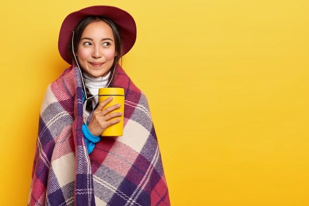 Jovem, calma e agradável, garota asiática em pé envolta em uma manta quentinha, segurando uma xícara de café para viagem, usa chapéu, aproveita o tempo para descansar