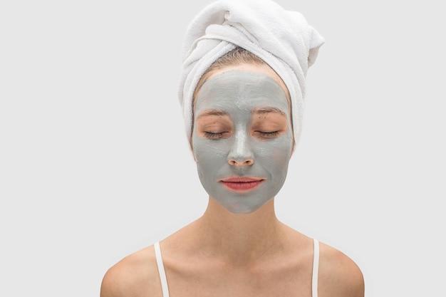 Jovem calma e pacífica com máscara facial mantém os olhos fechados. há uma toalha branca no cabelo.