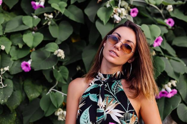 Jovem calma e tatuada em um vestido curto de estampa tropical de verão em uma praia rochosa com arbusto verde e flores rosa roxas
