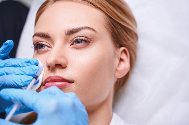 Jovem calma está lutando contra as rugas do rosto usando preenchimentos com ajuda profissional no salão de beleza