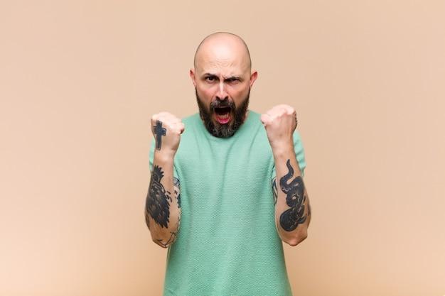 Jovem calvo e barbudo gritando agressivamente com uma expressão de raiva ou com os punhos cerrados celebrando o sucesso