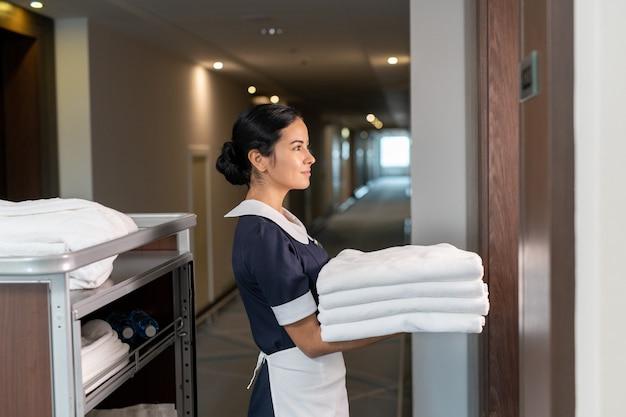 Jovem camareira trazendo lençóis limpos para uma das clientes do hotel