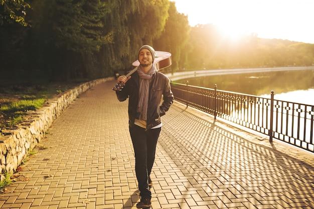 Jovem caminha à beira do lago e segurando o violão