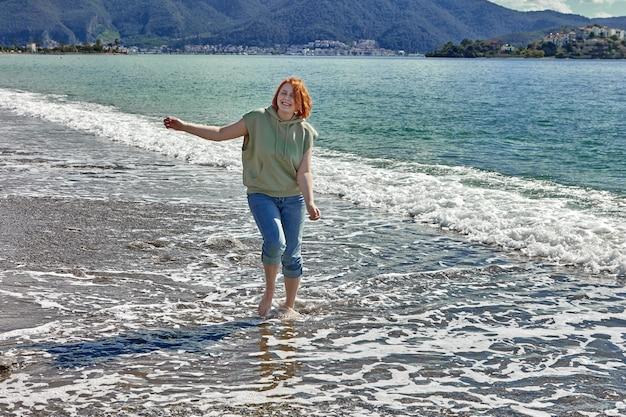 Jovem caminhando descalça na praia