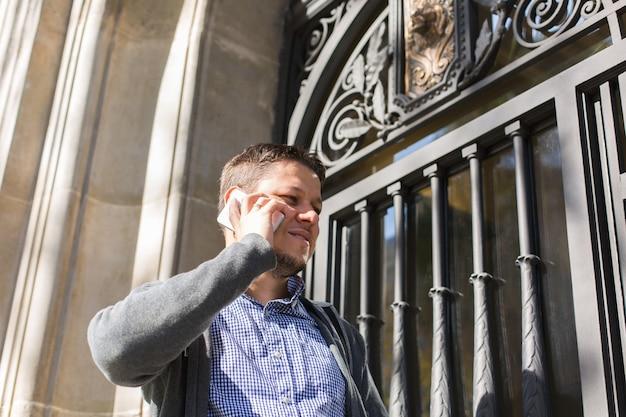 Jovem caminhando na rua e falando ao telefone