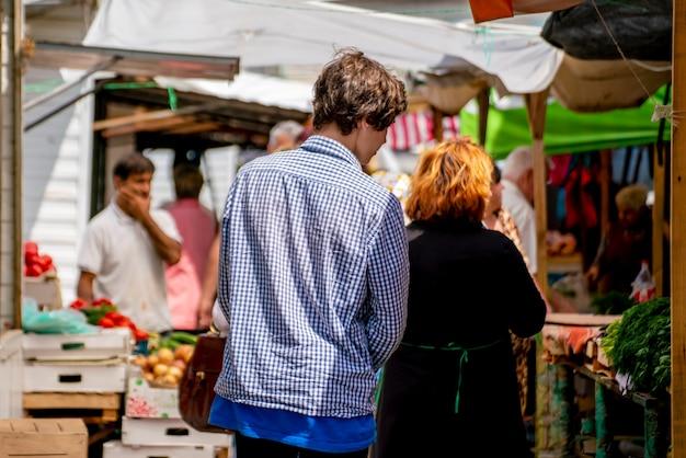 Jovem caminhando no meio da multidão no mercado da cidade