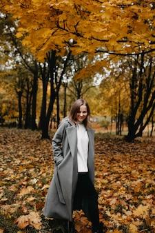 Jovem caminhando no parque de outono com um casaco longo