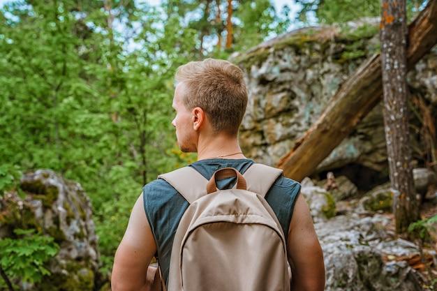 Jovem caminhando por uma floresta de pinheiros com pedras enormes cobertas de musgo