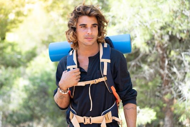 Jovem caminhante caucasiano passando as férias no acampamento