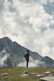 Jovem caminhante com uma mochila rodeada por montanhas sob um céu nublado na cantábria, espanha