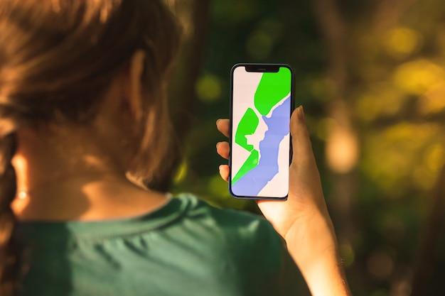 Jovem caminhante está usando o telefone celular para navegar na floresta, foto de fundo do bosque