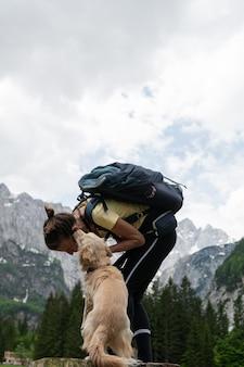 Jovem caminhante inclinando-se em direção a seu lindo cachorro beijando-a com belas montanhas ao fundo.