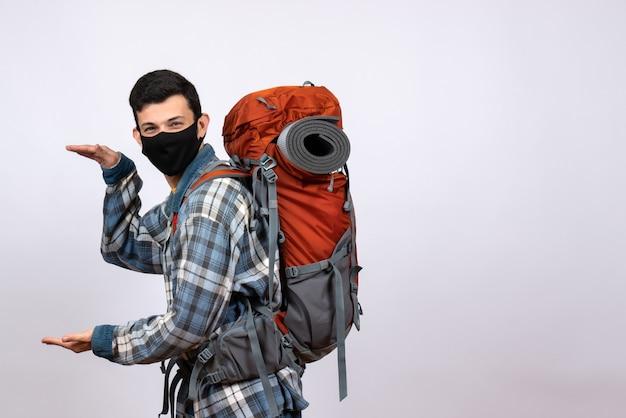 Jovem caminhante legal com mochila e máscara mostrando o tamanho com as mãos