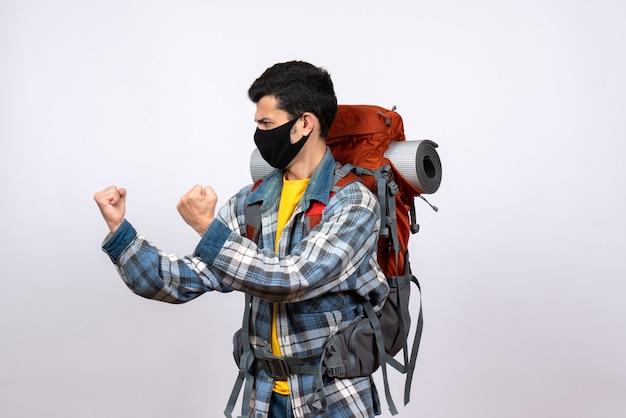 Jovem caminhante zangado de frente com mochila e máscara pronta para lutar